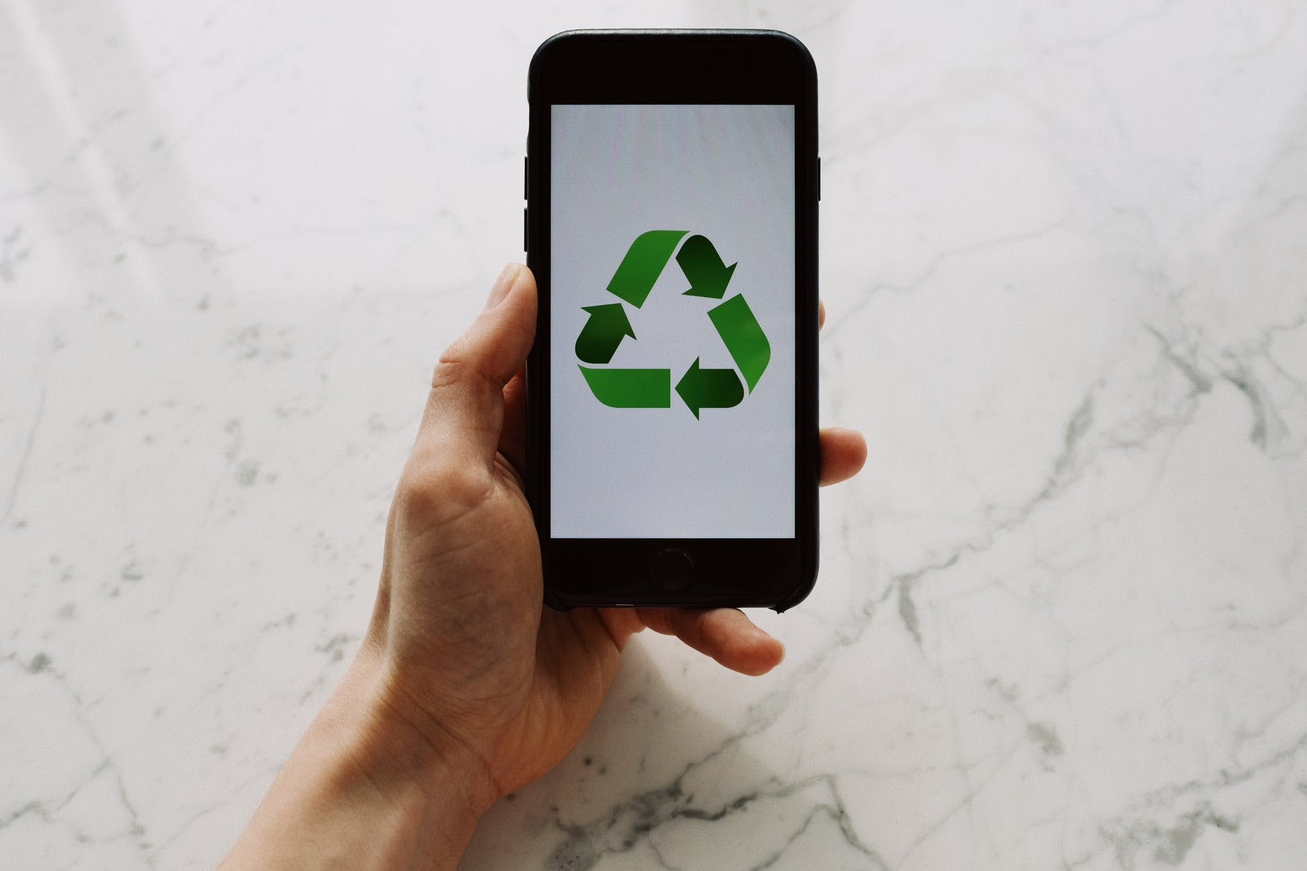 anonymous person showing recycle symbol on smartphone
